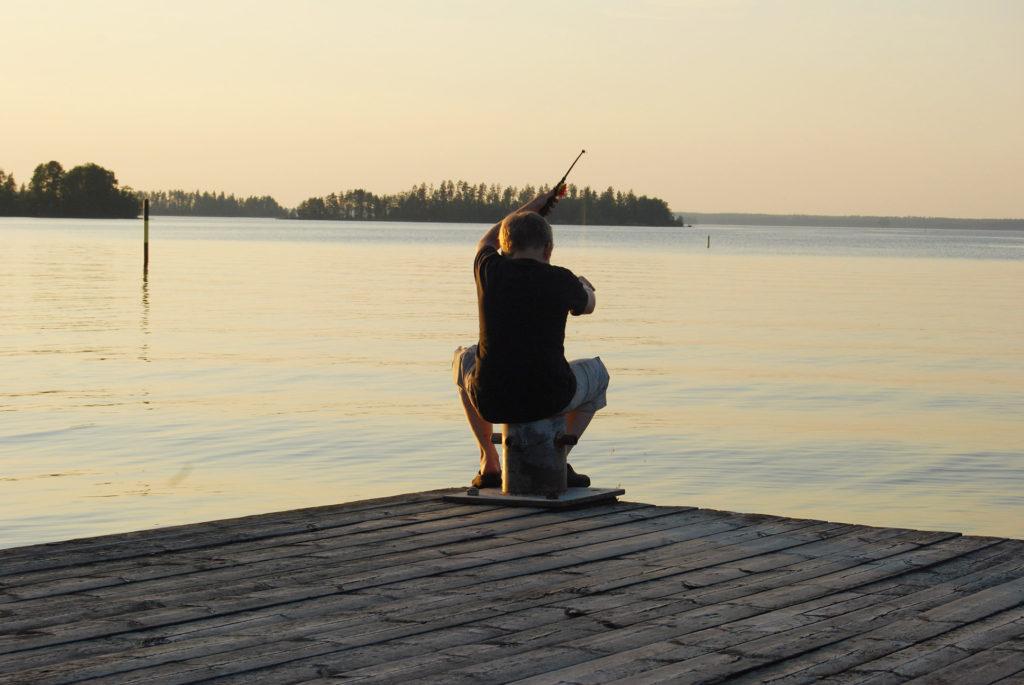 Poika kalastaa laiturilla.