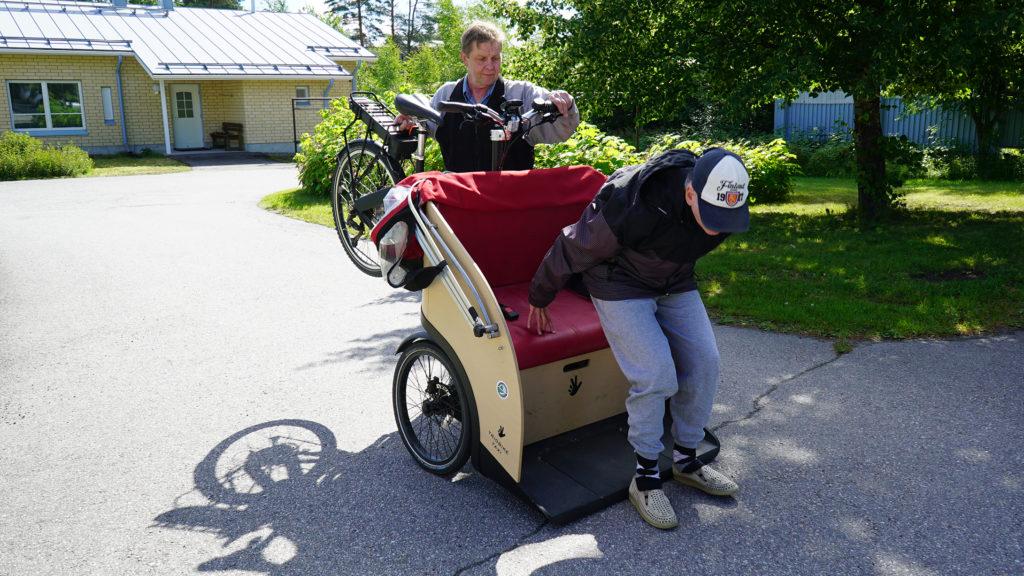Tuomon Niiranen näyttää, miten riksaa voi kallistaa, jotta kyytiin pääsy helpottuu.